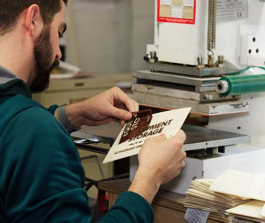 Worker inspecting sign lettering in workshop