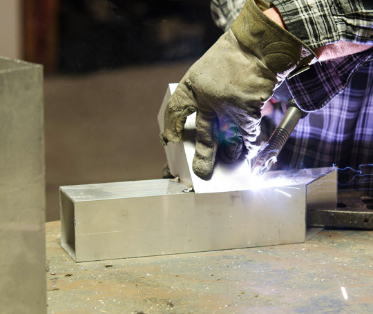 Man welding metal in sign workshop
