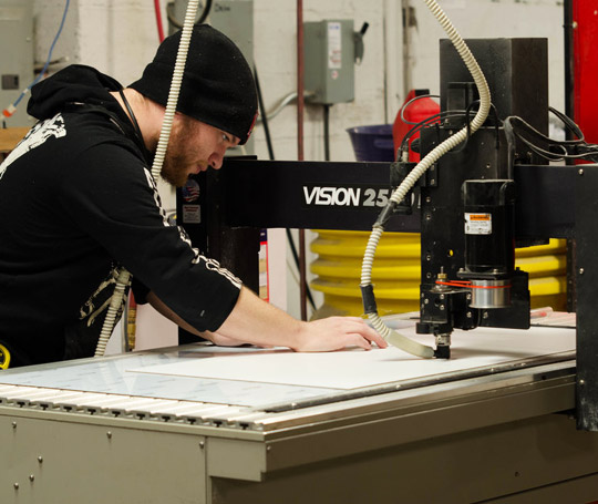 Worker using machinery to create signs in a workshop